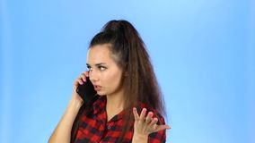 Pretty woman flirting by phone. Pretty woman is flirting by phone and smiling in the studio on blue background. She has beautiful face and wearing red and black stock footage