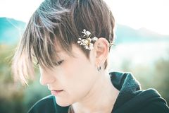 Pretty woman with a flower in her ear stock image
