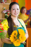 Pretty Woman in Flower Shop with Sunflowers Stock Photo