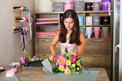 Pretty woman in the flower shop. Pretty young woman working in the flower shop Royalty Free Stock Photos