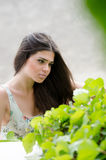 Pretty woman with flowered dress,greens on foreground Stock Image