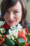 Pretty woman with flowers. A beautiful woman in her 30s with colour bouquet Stock Photo
