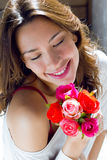 Pretty woman with flowers at home. Portrait of pretty woman with flowers at home Stock Image