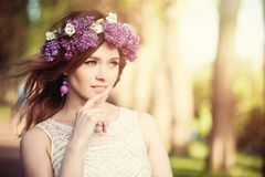 Pretty woman with flowers outdoors. Lilac flowers wreath, sunny light.  royalty free stock image