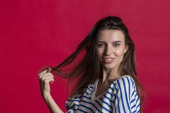 Studio shot of a lovely beautiful woman isolated against an empty red studio wall royalty free stock photography