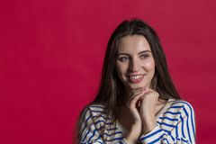 Studio shot of a lovely beautiful woman isolated against an empty red studio wall stock image