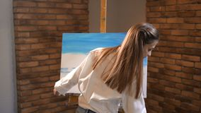 Pretty woman focused paints a picture. She fills the canvas with blue paint. 4K Slow Mo stock footage
