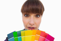 Pretty woman with fringe showing colour charts close up Royalty Free Stock Image