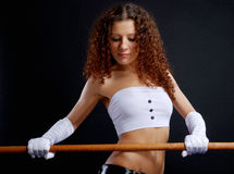 Pretty woman in front of the barrier. Serious woman is seizing a wood stick in front of herself. She is looking at the hurdle. Pretty girl is wearing white Royalty Free Stock Photos