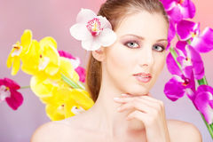 Pretty woman in front of  flowers Stock Photography