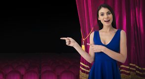 Pretty woman in front of red curtains indicates something about the theater show. Surprised pretty woman in front of red curtains indicates something about the royalty free stock image