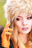 Pretty woman in fur hat talking on mobile phone. Portrait of pretty fashionable woman talking on mobile phone. Gorgeous young girl in fur winter hat and jacket Royalty Free Stock Images