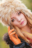 Pretty woman in fur hat talking on mobile phone. Portrait of pretty fashionable woman talking on mobile phone. Gorgeous young girl in fur winter hat and jacket Stock Photography