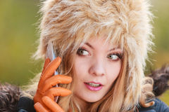Pretty woman in fur hat talking on mobile phone. Portrait of pretty fashionable woman talking on mobile phone. Gorgeous young girl in fur winter hat and jacket Royalty Free Stock Photography