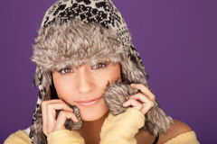 Pretty woman in fur trimmed winter hat. Pretty woman in a fur trimmed winter hat snuugling into the warmth of the earflaps against the winter chill Royalty Free Stock Photography