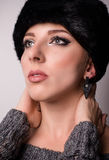 Pretty Woman in Furry Hat Looking Up Royalty Free Stock Images