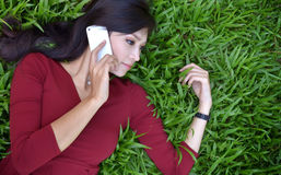 Pretty woman in the garden. Pretty woman making a phone call in the garden stock photography