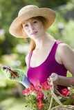 Pretty woman gardener. Pretty young woman cutting flowers in her garden Stock Photo
