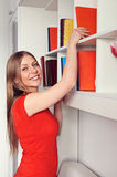 Woman getting book and smiling Stock Photography
