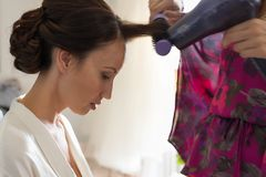 A pretty woman getting her hair styled and blow dried stock images