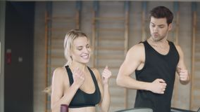 Pretty woman getting results on treadmill. Athletic lady making yes gesture. Smiling couple running on treadmill machine in fitness gym together. Pretty woman stock footage
