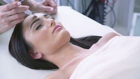 Pretty woman getting ultrasonic face treatment at beauty spa stock video