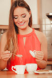 Pretty woman girl adding sugar to tea or coffee. Pretty woman adding sugar to tea or coffee at home. Gorgeous young girl with hot beverage relaxing in kitchen stock image
