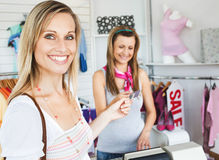 Pretty woman giving her card to the saleswoman. Smiling pretty woman giving her card to the saleswoman in a clothes store Royalty Free Stock Photo