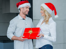 Pretty woman giving her husband a Christmas gift Royalty Free Stock Images