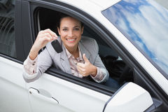 Pretty woman giving thumbs up while holding key Stock Photo