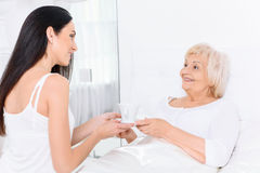 Pretty woman giving to her grandmother cup of tea. Giving care. Pleasant young lady giving cup of tea to her old grandmother on white background Royalty Free Stock Photography