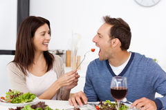 Pretty woman giving a tomato to her boyfriend Royalty Free Stock Images