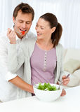 Pretty woman giving a tomato to his boyfriend Royalty Free Stock Photos