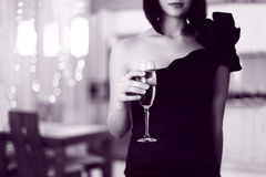 Pretty woman in glad rags, holding glass of drink Stock Photo