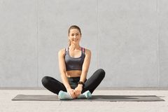 Pretty woman goes in for sport regularly, dressed in sportswear, sits crossed legs on mat in gym, has rest after yoga exercises, p royalty free stock photo