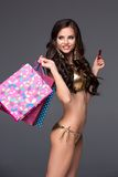 Pretty woman in gold bikini holding shopping bags Stock Photo