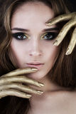Pretty Woman with Golden Makeup Stock Photography