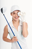 Pretty woman golfer on white background in studio. Pretty woman golfer posing with golf club and ball on white background in studio Royalty Free Stock Photography
