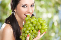 Pretty woman with grape Stock Images