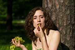 Pretty woman with grape snack Stock Images