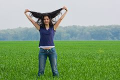 Pretty woman in grassfield. Portrait of a pretty young woman in a grassfield Royalty Free Stock Photos