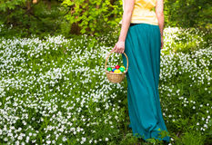 Pretty woman in green dress holding basket of easter eggs. Spring forest with white flowers Stock Photography