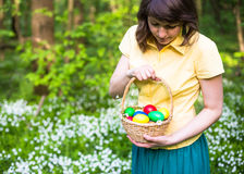 Pretty woman in green dress holding basket of easter eggs. Spring forest with white flowers Royalty Free Stock Photos