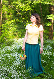 Pretty woman in green dress holding basket of easter eggs. Spring forest with white flowers Royalty Free Stock Photo
