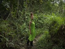 Pretty woman with green dress and rubber boots is walking through dense jungle royalty free stock photography