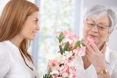 Pretty woman greeting mother with flowers smiling. Pretty woman greeting her mother at mother's day, giving flowers, both smiling stock image