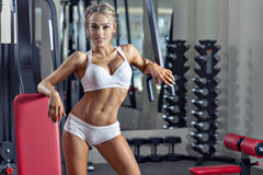 Pretty woman at the gym. Young sexy woman dressed in white clothes in the gym and looking at camera Stock Photos