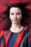 Pretty woman with hair in the wind, a designer dress in the style of futurism,. Red background stock photo