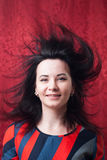 Pretty woman with hair in the wind, a designer dress in the style of futurism,. Red background stock image