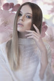 Pretty woman with hand near her face and flower background Royalty Free Stock Photo